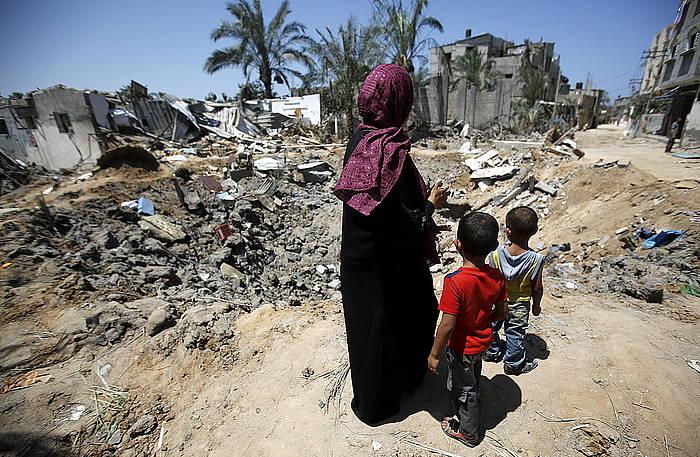 Familia bat bere etxea zegoen tokira begira, Gazan. ©Mohammed Saber / EFE