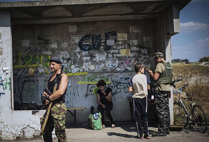 Emakume bat autobus geltoki batean, Donetseko kontrol portu batetik gertu. ©Roman Pilipey / EFE