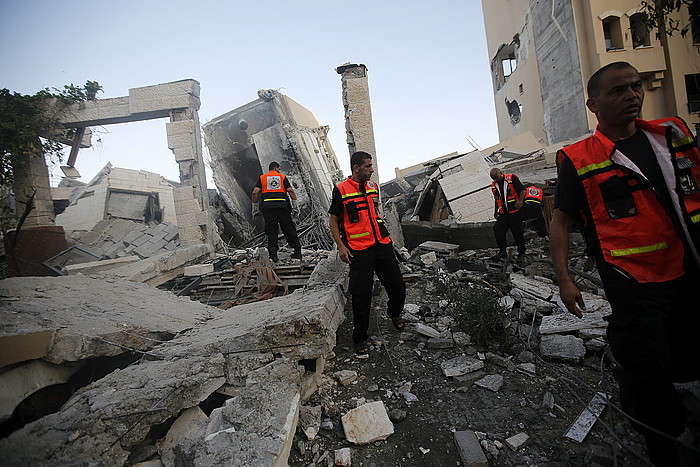 Langileak, suntsitutako eraikinen artean. Urteak beharko dituzte guztia berriz martxan jartzeko. ©Mohamed Saber / EFE