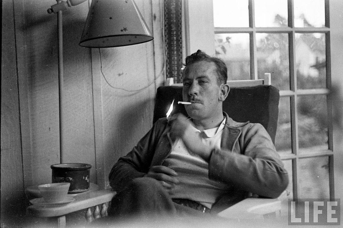 John Steinbeck idazle estatubatuarra, bere etxean, zigarro bat pizteko prest.