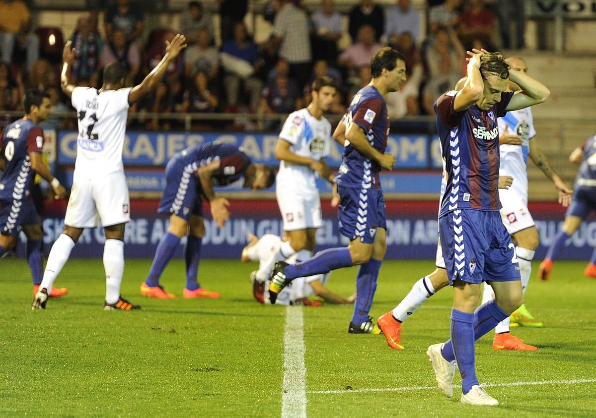 Javi Lara Eibarko jokalaria, burumakur. Atzean, Deportivoko jokalariak gola ospatzen. ©ANDONI CANELLADA / ARGAZKI PRESS