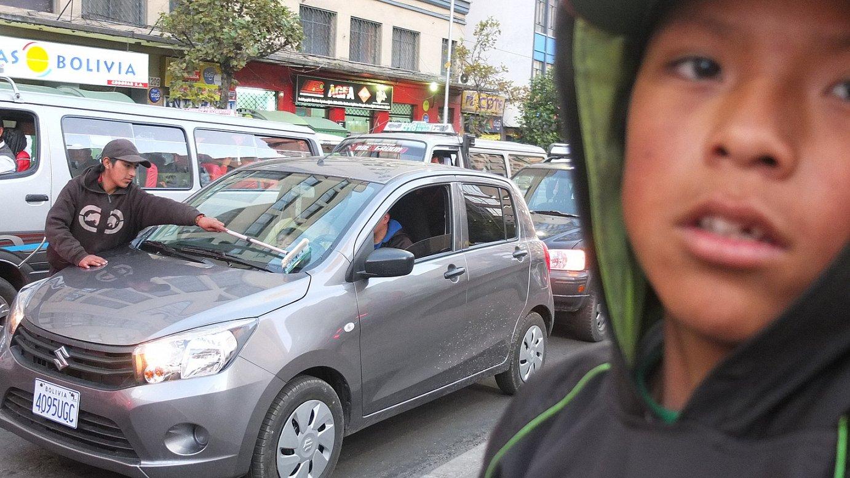 Haur batzuk semaforoetan gelditutako autoen beirak garbitzen, La Pazeko kaleetan. ©PAULINE BAROU