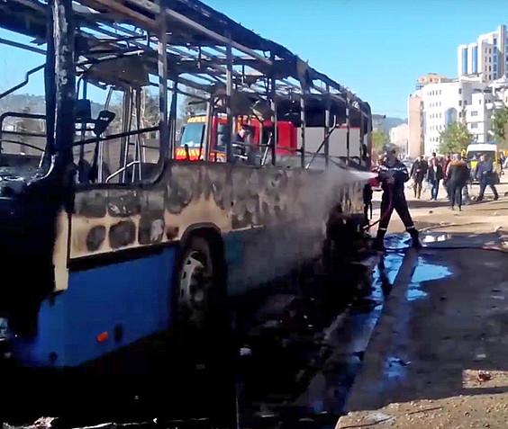 Suhiltzaileak erretako autobus baten sua itzaltzen, herenegun, Bejaian. ©BERRIA
