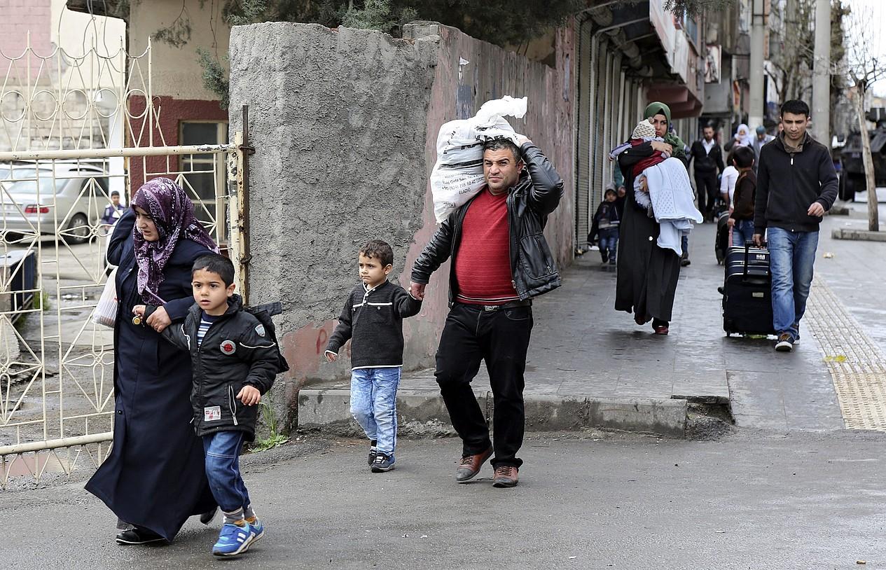 Diyarbakirgo Baglar barrutiko herritarrak ihesean, iazko martxoan, armadak hiriari eraso egin ostean. ©STR / EFE