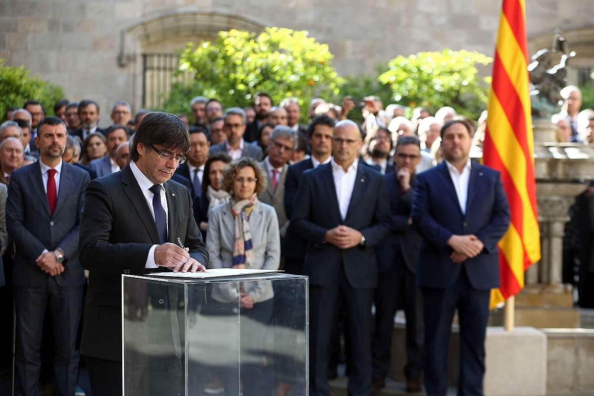 Carles Puigdemont Kataluniako presidentea, gobernu osoak sinatutako agiria izenpetzen. ©TONI ALBIR / EFE