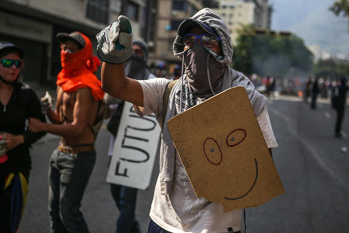 Oposizioko jarraitzaileak Poliziari aurre egiten Caracasen, herenegun. 20 urteko gazte bat hil zen istiluen eremuan. ©CRISTIAN HERNANDEZ / EFE