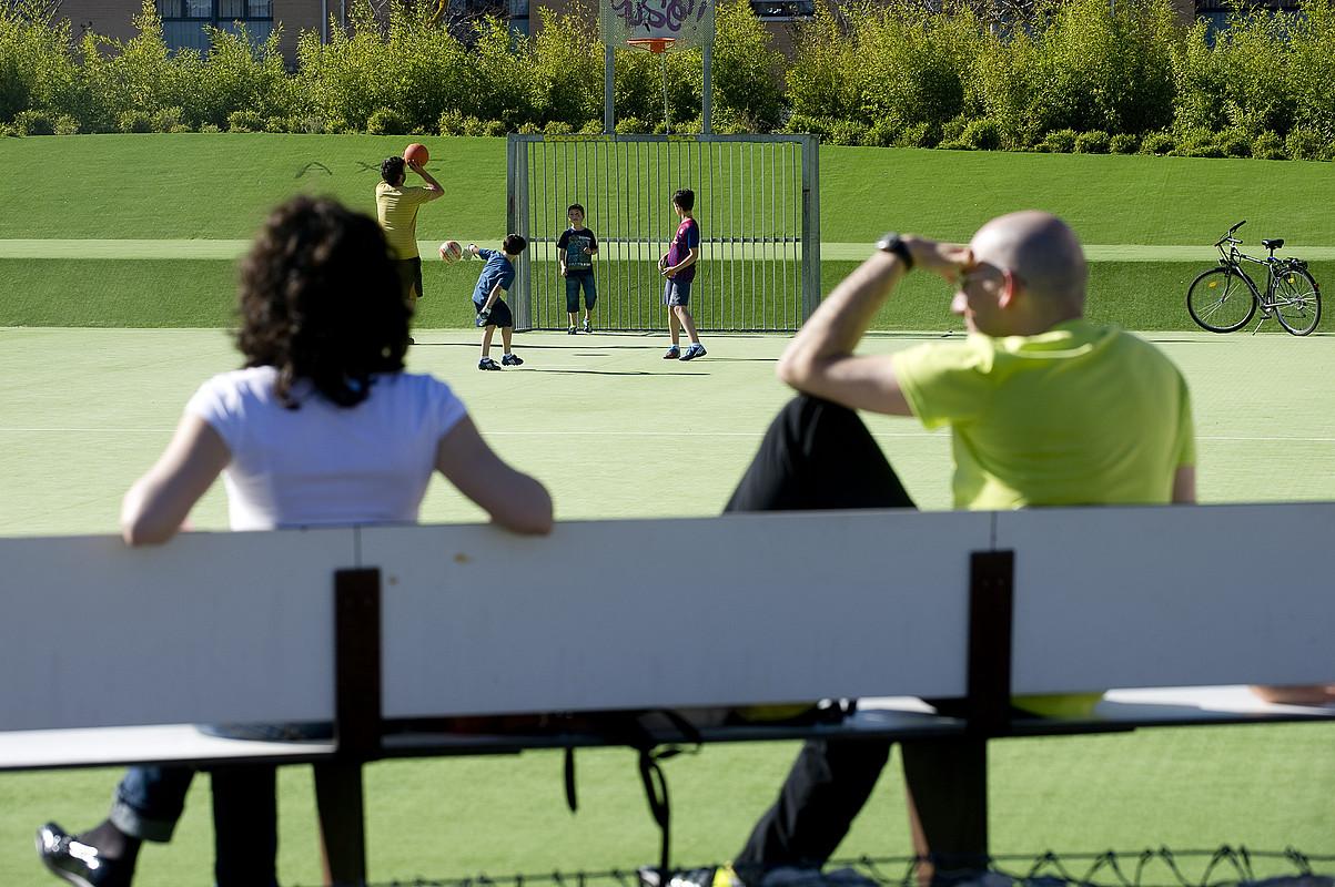 Emakume bat eta gizon bat, parke baten inguruan. Atzean, umeak, jolasean. ©RAUL BOGAJO / ARGAZKI PRESS