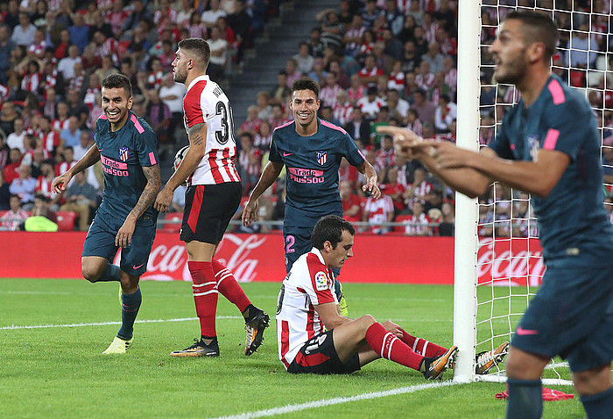 Atletico Madrileko jokalariak 0-1ekoa ospatzen. Tartean dira Unai Lopez eta Iñigo Lekue Athleticeko jokalariak, eserita, burumakur. ©LUIS TEJIDO / EFE
