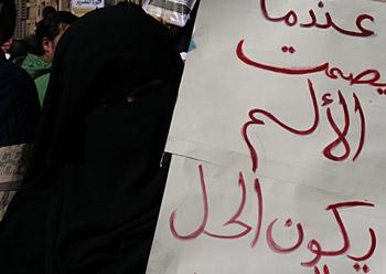 Tahrir plazan elkarretaratutako emakume bat, goitik behera tapatuta, burka beltz batekin (2011-02-18)