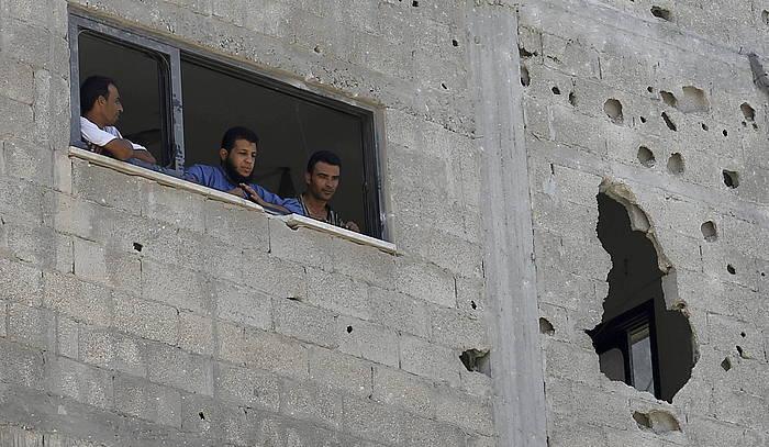 Palestinarrak bonbardaketek kaltetutako etxe bateko leihoan, Gazan.