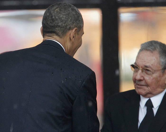 Barack Obama eta Raul Castro, Nelson Mandelaren aldeko hiletan, elkarri bostekoa ematen.