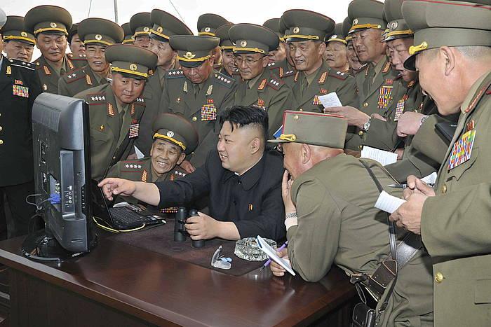 Kim Jong-Un, hainbat soldadurekin ordenagailu bati begira,  apirilean.