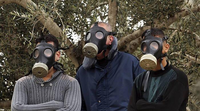 Hiru lagun, gas maskarak jantzita, Nablusen eginiko protesta batean.