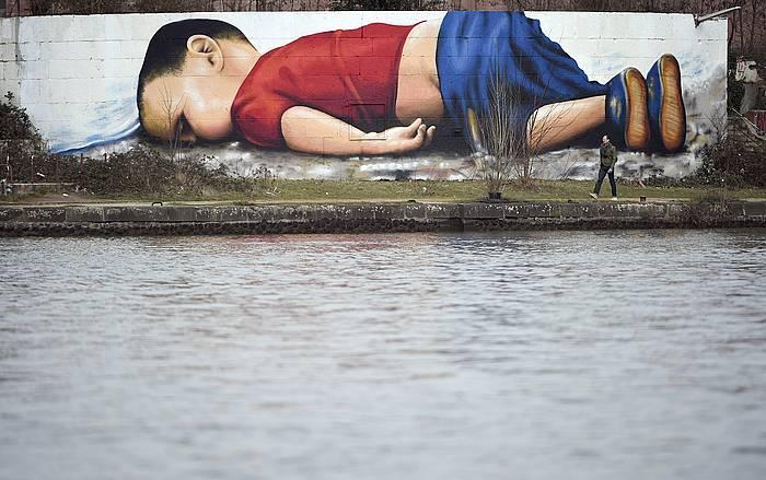 Egeo itsasoan hildako haurraren omenez Francforten eginiko murala. Jatorrizko argazkia Nilufer Demir Turkiako argazkilariak atera zuen.