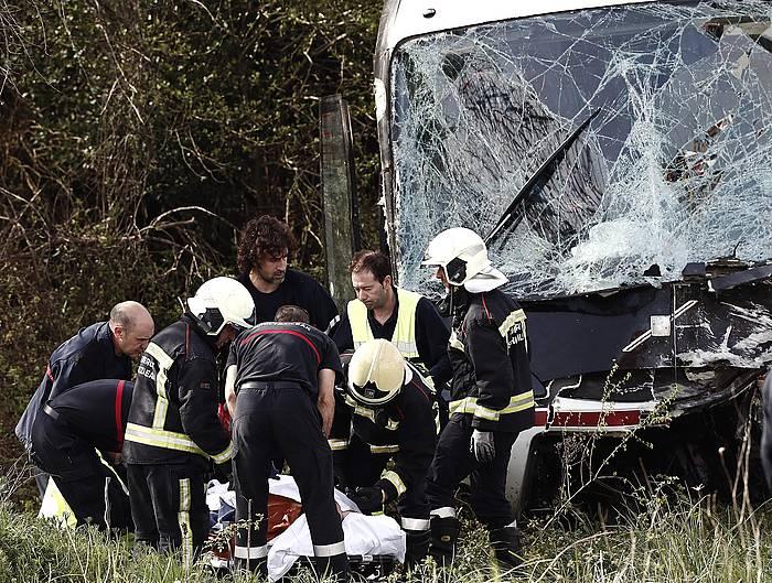 Larrialdi zerbitzuak Lantzen, istripua gertau den tokian lanean, ezbeharra izan duen autobusa atzean dutela. / ©JDIGES, EFE