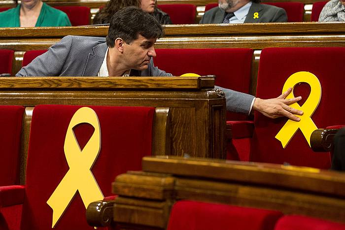 Sergi Sabria ERCko diputatua, Kataluniako Parlamentuaren gaurko osoko bilkuran, auzipetutako diputatu independentisten omenezko xingola hori bat egokitzen. / ©Quque Garcia, EFE