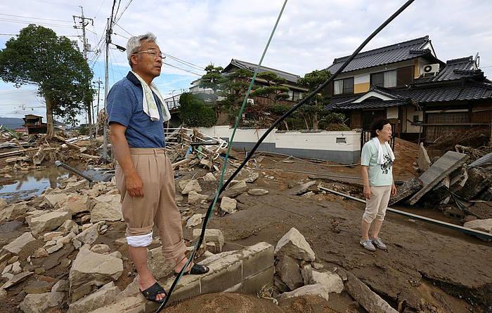 Bi japoniar lurrez estalitako errepidean eta hondatutako eraikinen artean oinez, Okayama eskualdeko Kurashiki hirian.