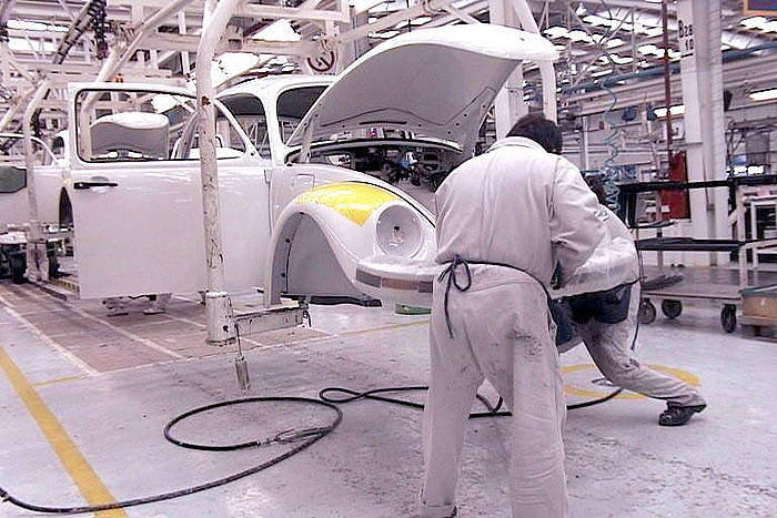 Volkswagenek Pueblan duen lantegiko langileak, 'beetle' edo kakalardo batekin lanean. /