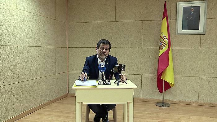 Jordi Sanchez, Espainiako bandera eta erregearen argazkia atzean dituela. /