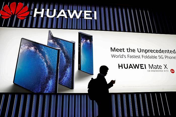 Erabiltzaile bat Huawei denda baten alboan.