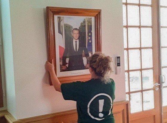 Bizi mugimenduko kide bat, Emmanuel Macron Frantziako presidentearen erretratu bat kentzen, Bardozeko herriko etxean.