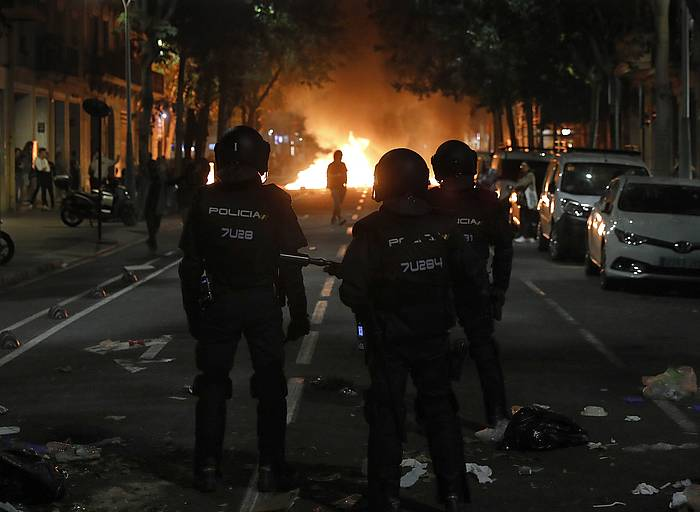 Hiru polizia, Bartzelona erdialdean jarritako barrikada bati begira, astearte gauean.