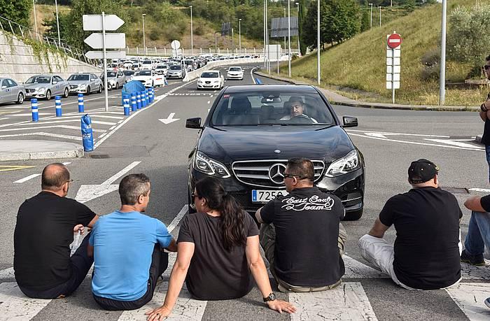 Bilboko taxi gidari talde bat Uber eta Cabify enpresen jardunaren kontra protestan, iazko uztailean, Bilboko aireportuan.