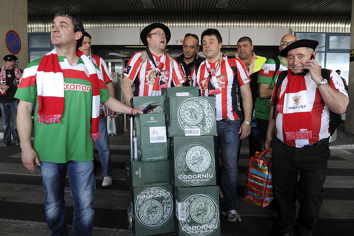 Athleticeko zale batzuk xanpaina botilez betetako kaxekin, atzo, Bukaresteko aireportura iritsi berritan. / JON ESKUDERO