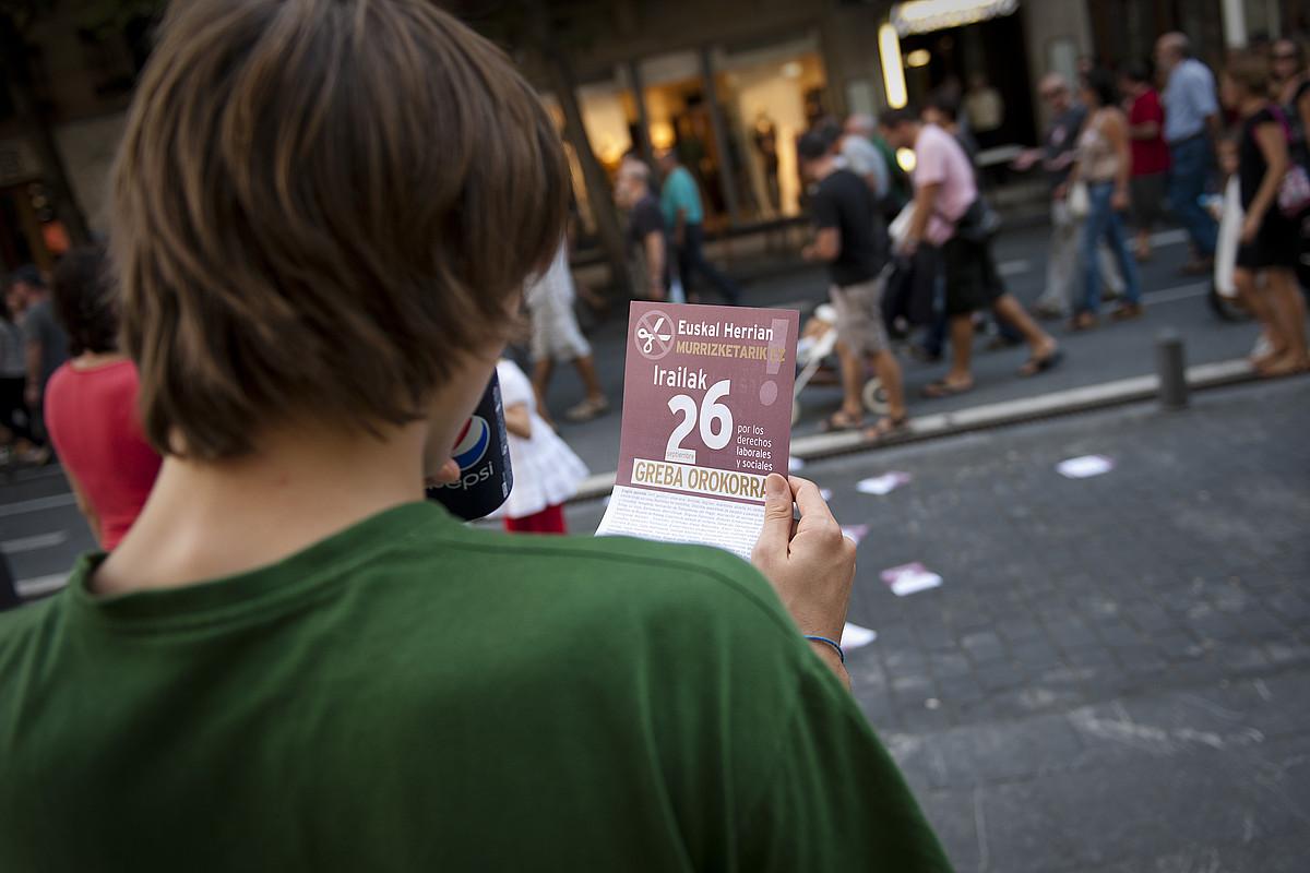 Gazte bat greba orokorrera deitzen duen kartel bat eskuetan, Donostian, sindikatu abertzaleek larunbatean eginiko manifestazioan. ©GARI GARAIALDE / ARP