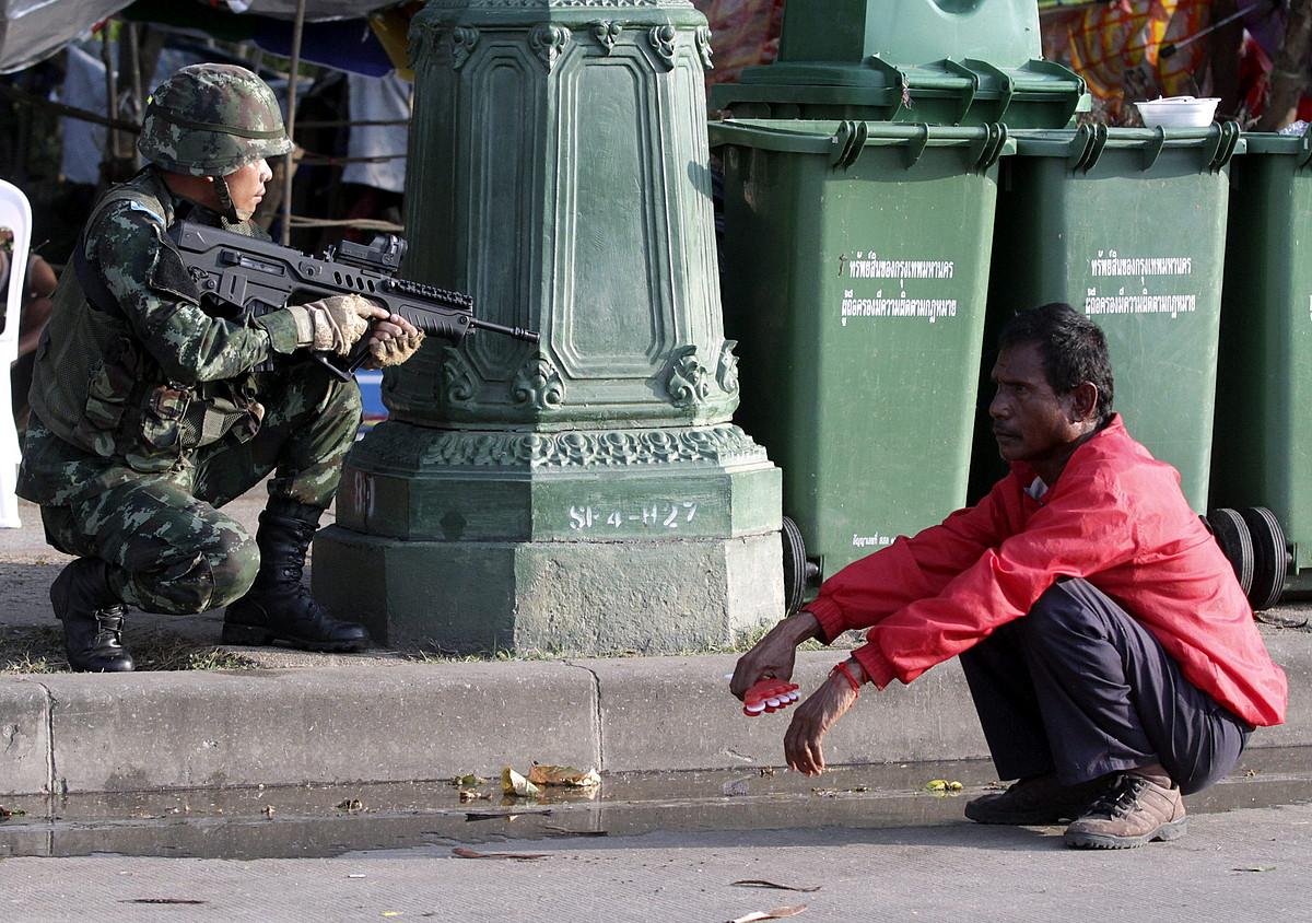 Soldadu bat, posizioa hartuta, Bangkok hiriburuan, militarrek atxikitako <em>elastiko gorrietako</em> manifestari baten ondoan.