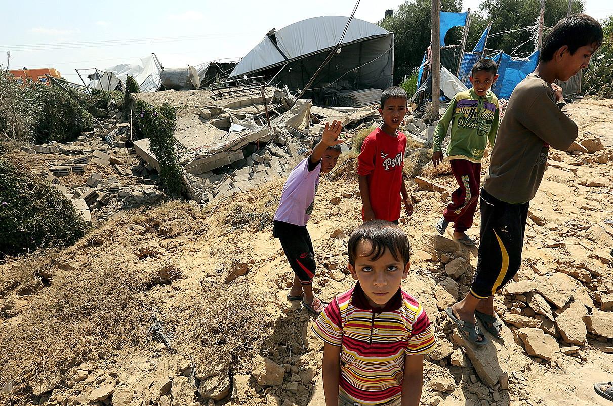 Haur palestinarrak Rafah inguruan (Gaza), Israelgo hegazkin militarrek suntsitutako etxe baten ondoan.