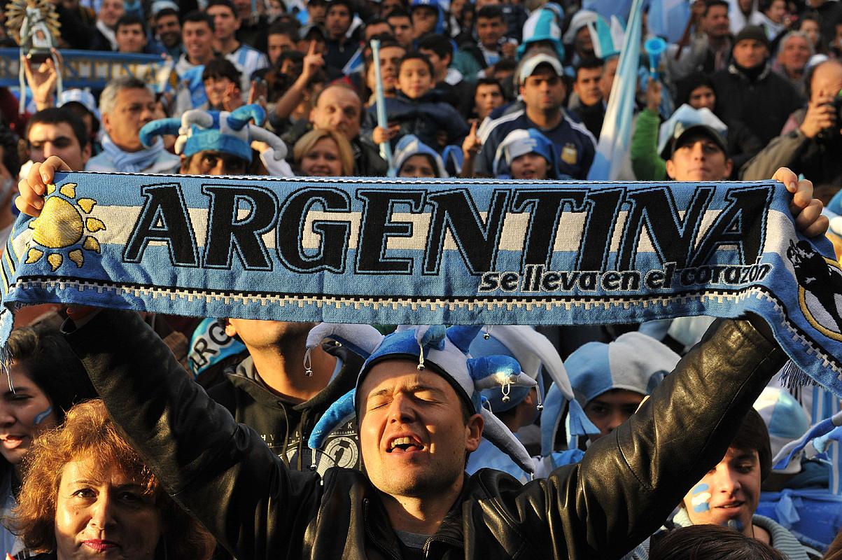 Zale bat, <em>Argentina bihotzean eramaten da</em> leloa duen bufanda erakusten, Buenos Airesko ospakizunetan.</em> / E. G. M. / EFE