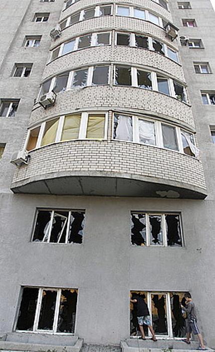 Bi haur, Donetsken, eraikin bateko leiho apurtuei begira.