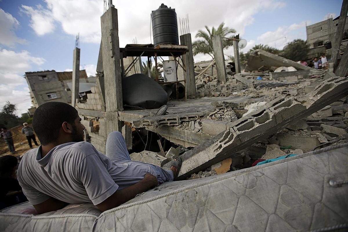 Gazako herritar bat, Israelek suntsitutako eraikin baten hondakinei begira, Khan Yunis hirian.