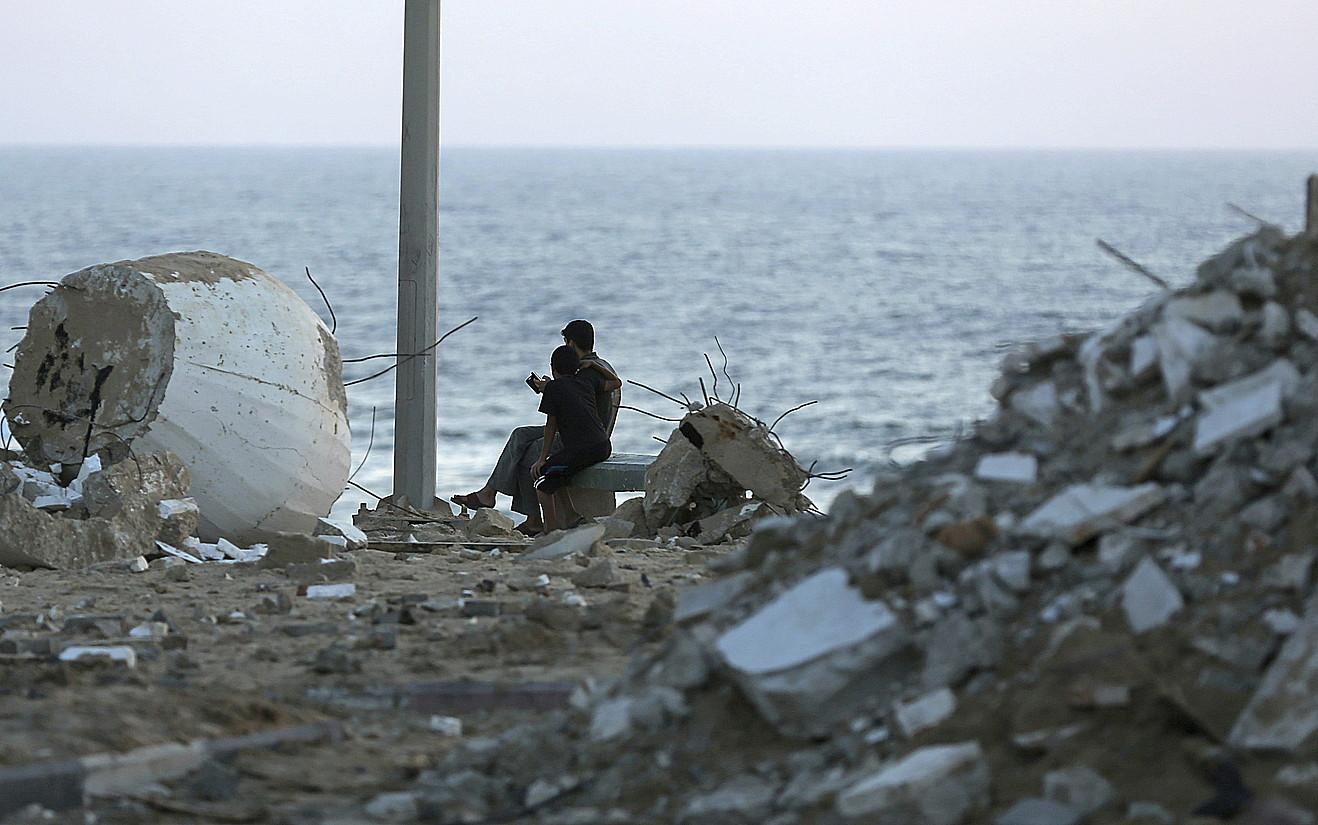 Bi palestinar, Gaza hiriko hondartzan, bonbardaketek eragindako txikizioaren artean, atzo.