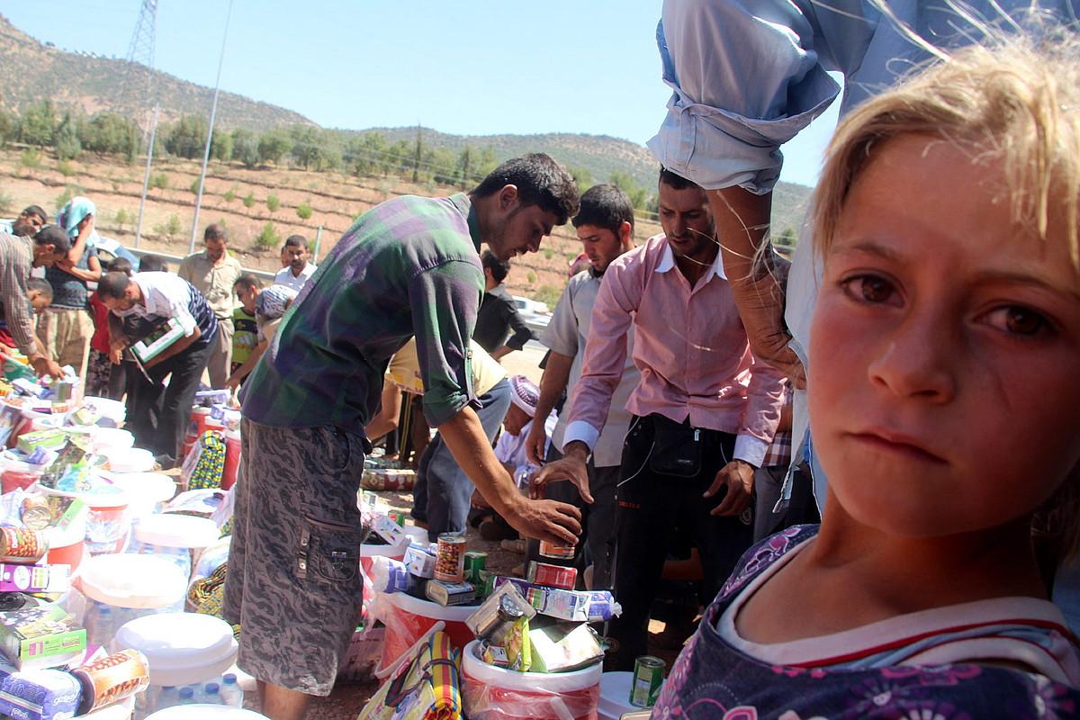 Iheslari yezidiak, giza laguntza jasotzen, Dohuken. Hego Kurdistanera 700.000 errefuxiatu baino gehiago iritsi dira.