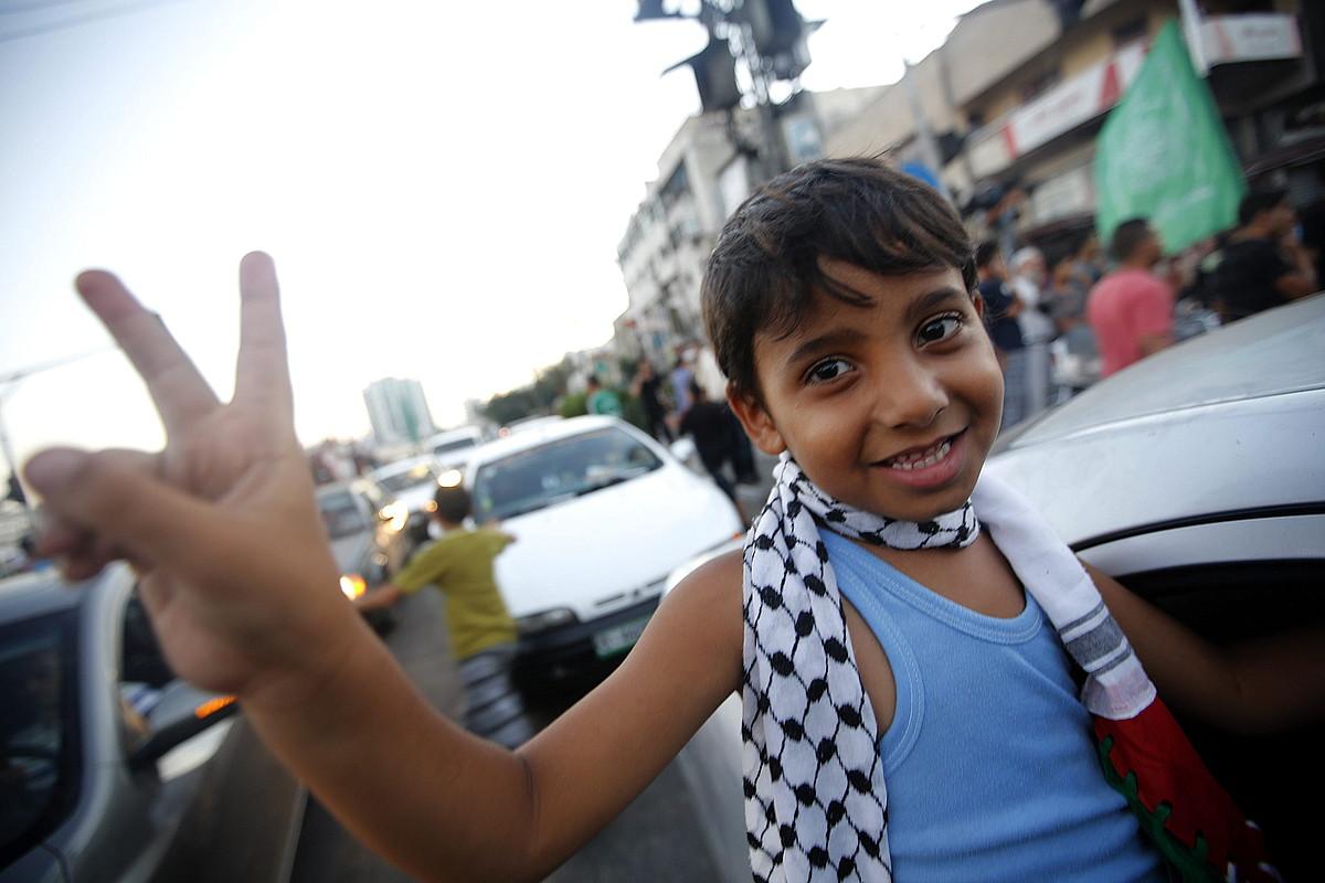 Gazan ehunka lagun irten ziren atzo iluntzean kalera, su-etena ospatzera. Irudian, haur bat.