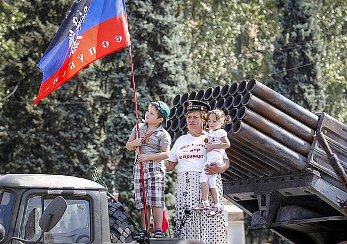 Emakume bat bere bi haurrekin, armadako ibilgailu suntsitu batean, Donetsk hirian, iragan astean.