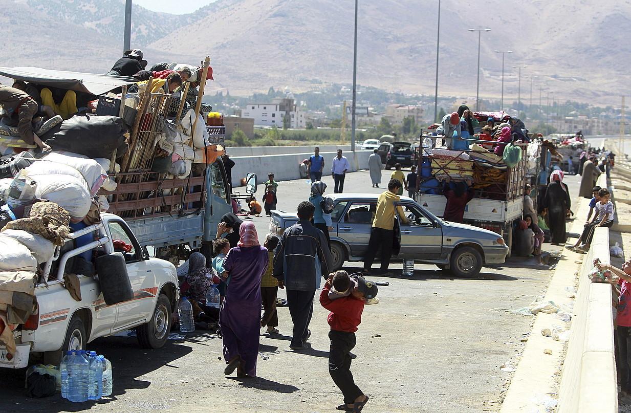 Hainbat errefuxiatu, Libanoko muga zeharkatzeko itxaroten, hilaren 8an, Masnaa herrian, Sirian.