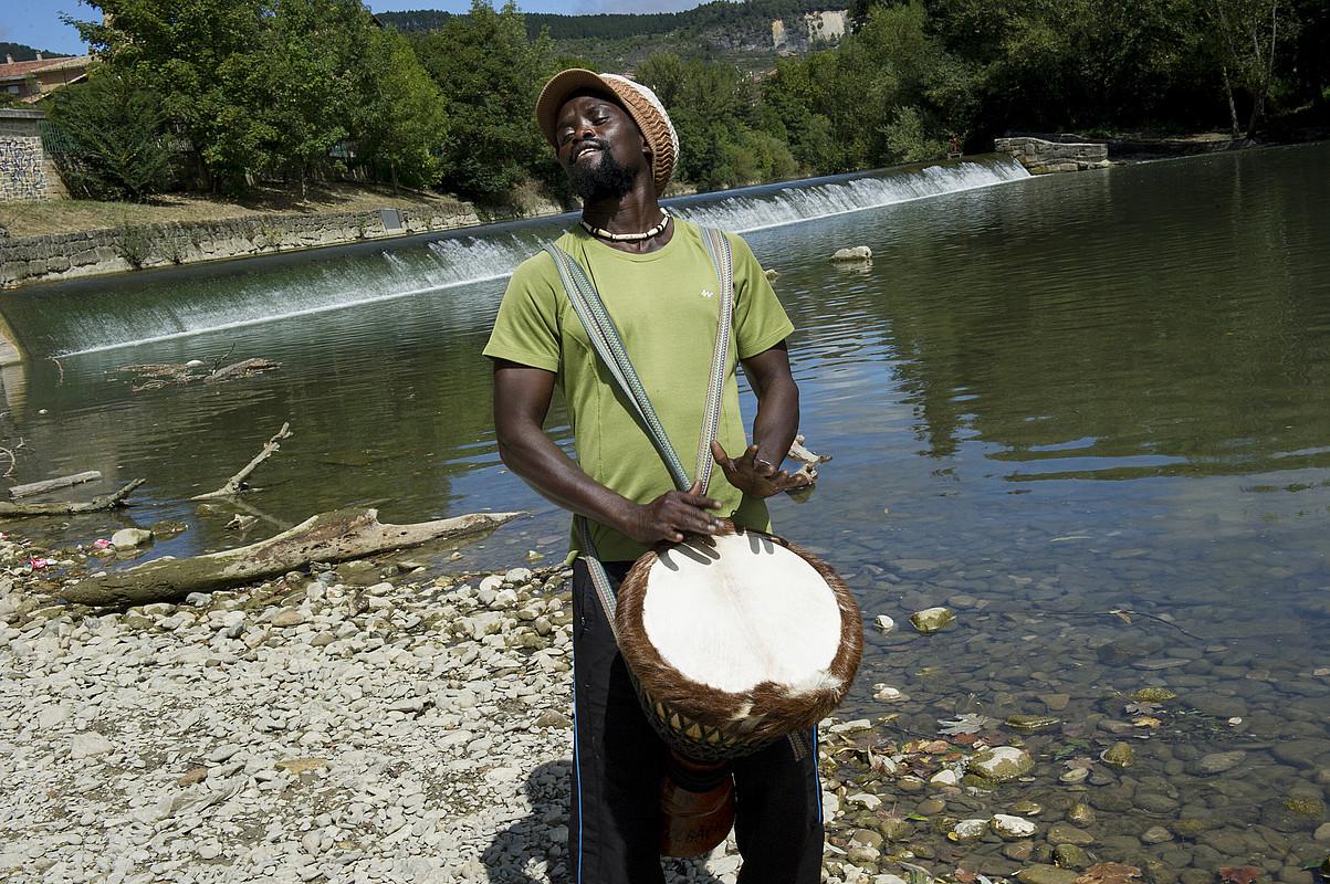Jacques Diatta perkusio jotzaile eta irakaslea djembea jotzen, Iruñean, Arga ibaiaren ertzean. / IÑIGO URIZ / ARGAZKI PRESS