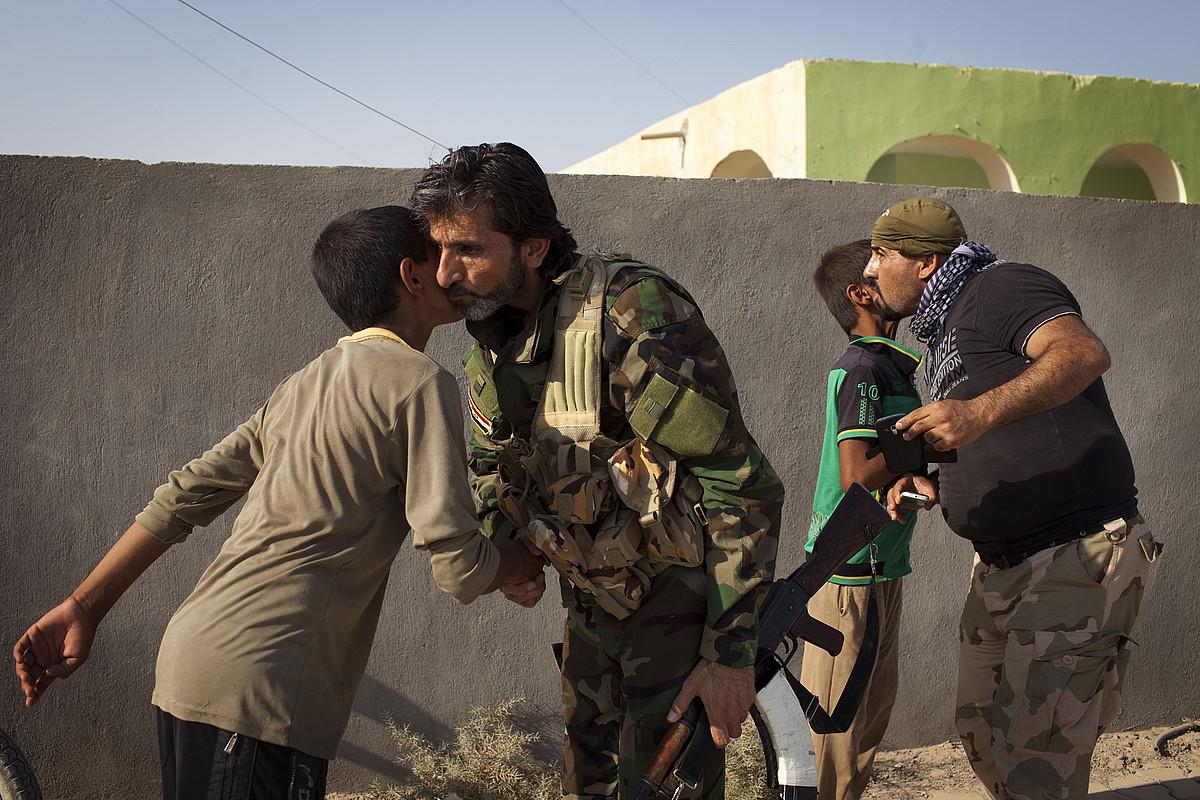 Irakeko armadako soldaduak, Amerliko haurrei musu ematen, herria askatu berritan.