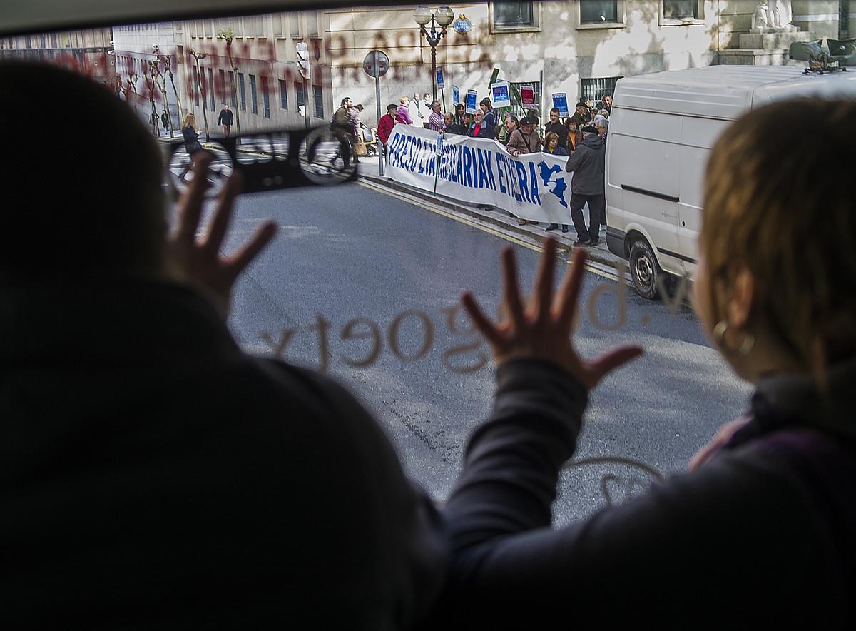 Presoak bisitatzera joateko autobus bateko bidaiariak, mobilizazio batean dauden pertsonak agurtzen.
