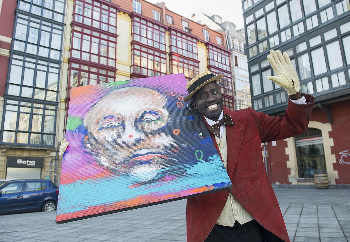Cheikhou Ba artistak Chocolat <em>clown</em>-aren omenez sortutako margolana eskuetan du Mbaye Senek, pailazoaren rola jokatzen duen aktoreak.