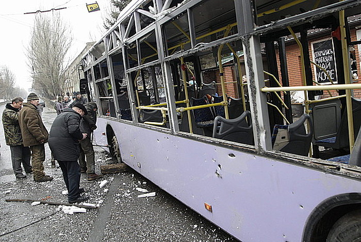 Donetskeko herritarrak, mortero batek suntsitutako trolebusari begira, atzo.