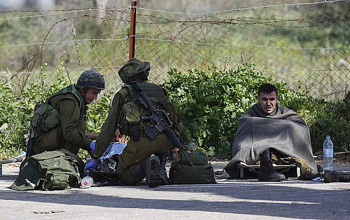 Soldadu israeldarrak, Hezbollahen erasoan zauritutako bi kide artatzen, Xebaako etxaldeetan.