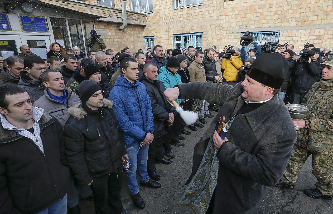 Apaiz ortodoxo bat frontera bidali dituzten Ukrainako soldaduei bedeinkazioa ematen, atzo, Kieven.