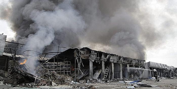 Suhiltzaile bat Ukrainako armadak bonbardatutako saltoki bateko sutea itzali nahian, atzo, Donetsk hirian.