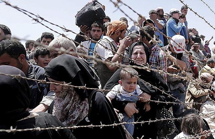Siriako errefuxiatuak Raqqa probintziatik Turkiako Akçakale hirira muga gurutzatzeko zain, atzo.