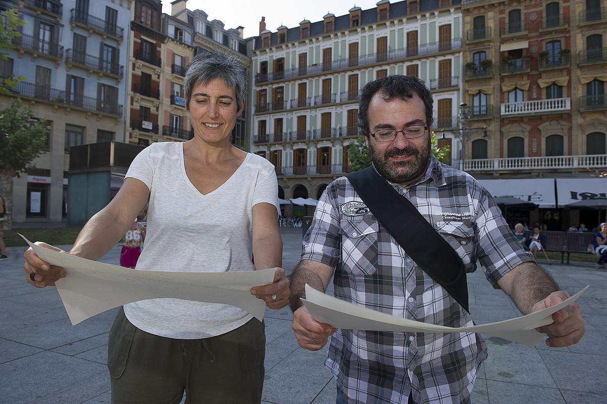 Paula Kasares eta Ricardo Feliu, elkarrizketarako erabili dituzten mapei begira, Iruñeko Gazteluko plazan. / ARGAZKIAK: IÑIGO URIZ / ARGAZKI PRESS