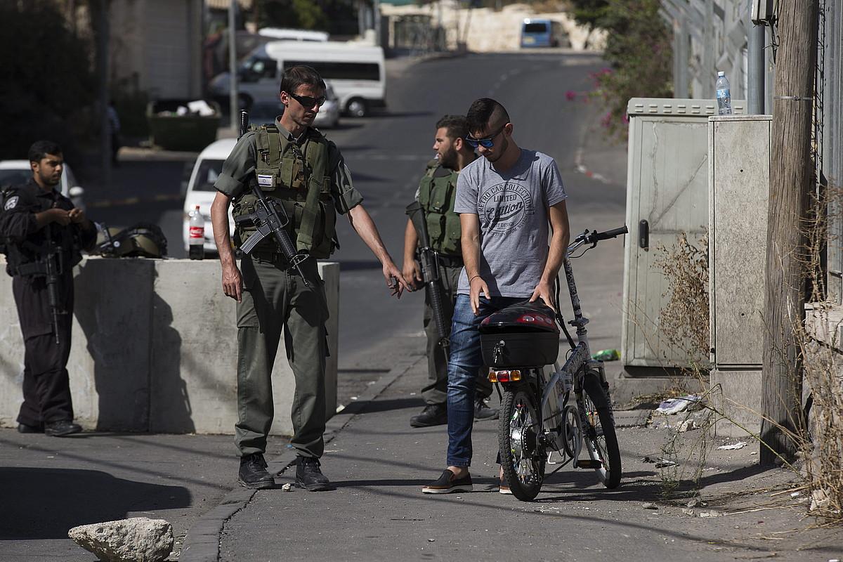 Polizia israeldarrak, Jerusalemgo Al-Amud auzoko sarreran ezarritako kontrolean, atzo, palestinar bat miatzen. ©ATEF SAFADI / EFE